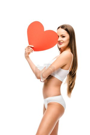 beautiful girl in underwear holding heart shaped card and looking at camera isolated on white