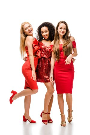 Photo for Beautiful multiethnic girls in red dresses looking at camera and posing on white background - Royalty Free Image