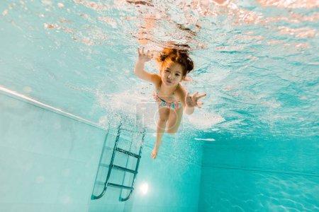cute kid swimming underwater in blue water in swimming pool