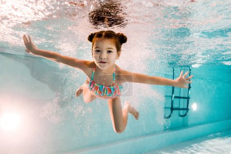 Photo for Adorable kid swimming underwater in blue water in swimming pool - Royalty Free Image