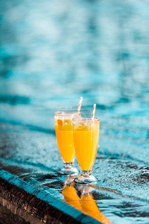 Photo pour Cocktails orange avec des pailles debout près de la piscine - image libre de droit