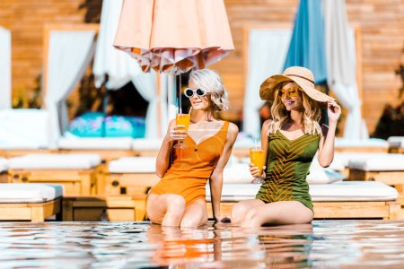 Photo for Smiling beautiful girls in swimsuits and sunglasses relaxing at poolside with cocktails - Royalty Free Image
