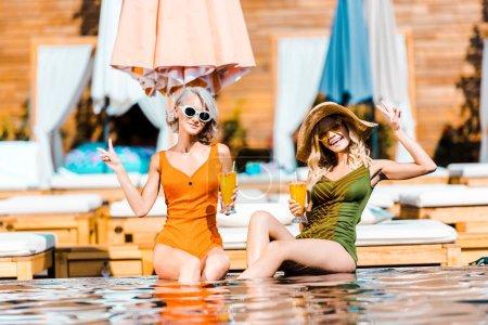 Foto de Felizes mujeres en trajes de baño y gafas de sol relajantes en piscina con cócteles - Imagen libre de derechos