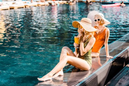 Photo for Beautiful women sitting at poolside with glass of cocktail - Royalty Free Image