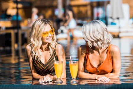 Foto de Mujeres con estilo rubias joven relajantes en piscina con cócteles - Imagen libre de derechos