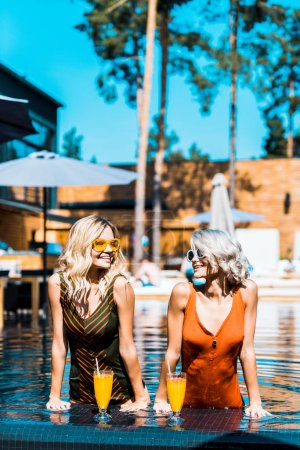 Photo for Blonde stylish girls relaxing in swimming pool with cocktails - Royalty Free Image