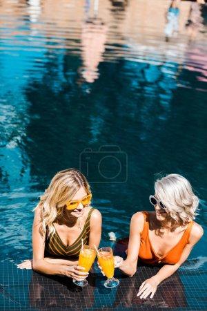 Foto de Atractiva rubia perno encima de muchachas relajantes en piscina con vasos de jugo de naranja - Imagen libre de derechos