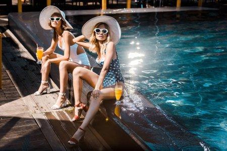Foto de Atractivo pin a mujeres en traje de baño relajante en la piscina con cócteles - Imagen libre de derechos