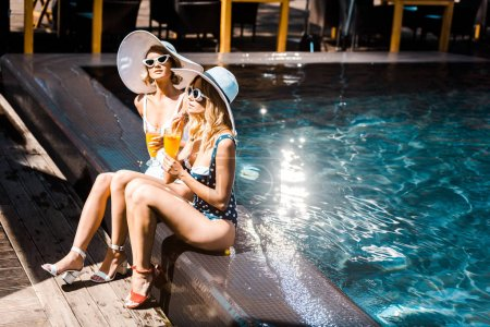 Photo for Attractive happy women relaxing at poolside with orange cocktails - Royalty Free Image