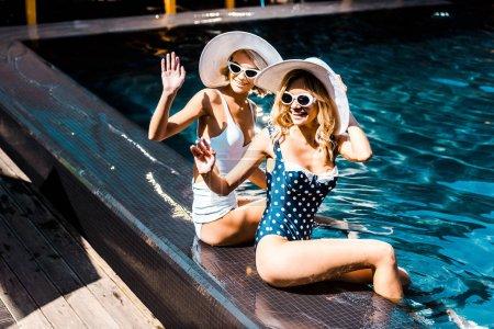 Photo pour Filles heureuses en lunettes de soleil et chapeaux agitant dans la piscine - image libre de droit