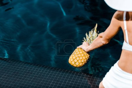 Photo for Partial view of girl posing with pineapple near swimming pool - Royalty Free Image