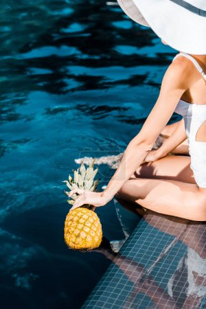 Photo for Young woman in swimwear and hat posing with fresh pineapple at poolside - Royalty Free Image
