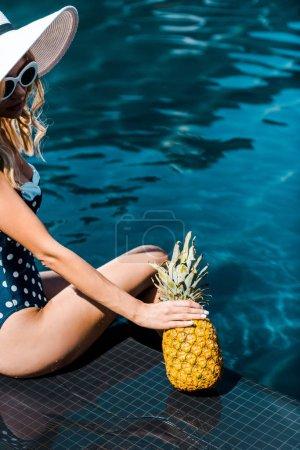 young woman in swimwear posing with pineapple near swimming pool