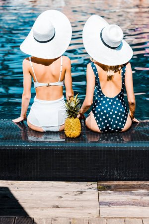 Photo for Back view of pin up girls in swimsuits and hats sitting with pineapple at swimming pool - Royalty Free Image