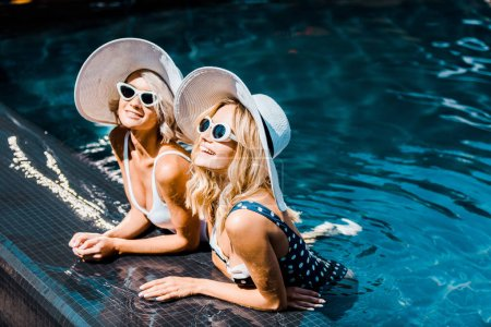 Photo for Attractive girls in sunglasses and hats posing in swimming pool - Royalty Free Image