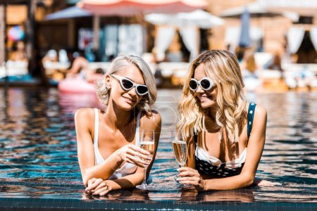 Photo for Beautiful blonde girls in sunglasses relaxing in swimming pool with champagne glasses - Royalty Free Image