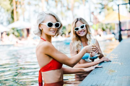 Photo for Blonde women in sunglasses clinking champagne glasses and resting in swimming pool - Royalty Free Image