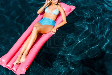 Photo for Young pin up woman in swimsuit resting on pink inflatable mattress in swimming pool - Royalty Free Image