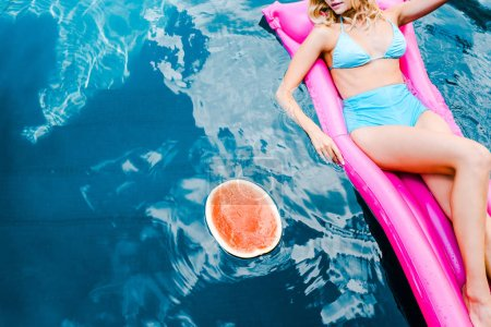 Photo for Cropped view of girl in swimsuit resting on pink inflatable mattress in swimming pool with watermelon - Royalty Free Image