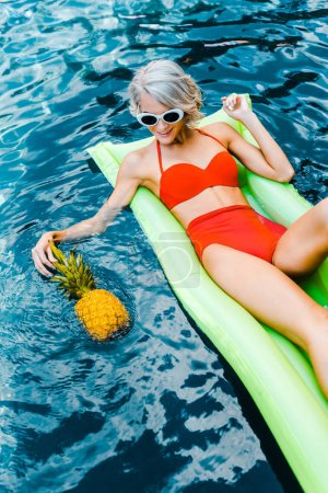 Photo for Happy girl in pin up swimsuit relaxing on green inflatable mattress in swimming pool with pineapple - Royalty Free Image