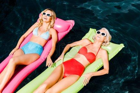beautiful women sunbathing on inflatable mattresses in swimming pool