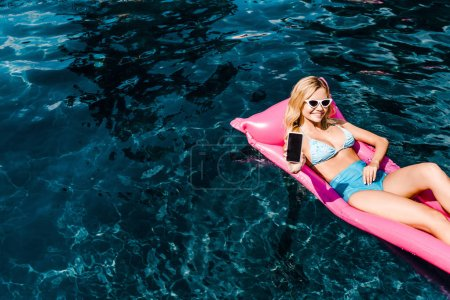 Photo for Beautiful girl in swimsuit lying on pink inflatable mattress in swimming pool and showing smartphone with blank screen - Royalty Free Image
