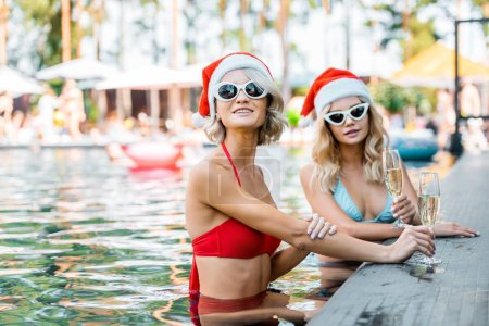 Foto de Atractivas chicas sonrientes en trajes de baño y sombreros de santa sosteniendo copas de champagne y sentado en la piscina - Imagen libre de derechos