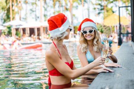 Photo pour Heureuse femme maillots de bain et des chapeaux de santa tenant des coupes à champagne et assis dans la piscine - image libre de droit