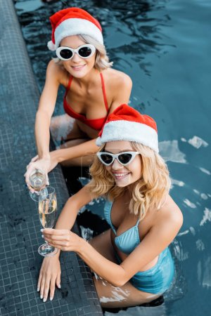 Photo for Overhead view of beautiful happy girls in swimsuits and santa hats holding champagne glasses and relaxing in swimming pool - Royalty Free Image