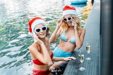 Foto de Chicas felices en trajes de baño y sombreros de santa, hablando de smartphones mientras estaba sentado en la piscina con copas de champagne - Imagen libre de derechos
