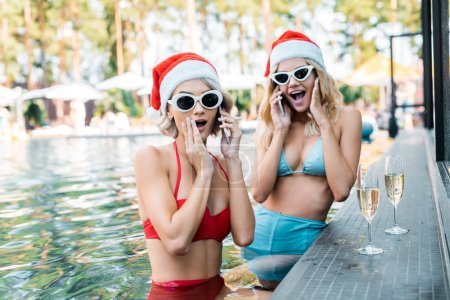 Photo for Shocked women in swimsuits and santa hats talking on smartphones while sitting in swimming pool with champagne glasses - Royalty Free Image
