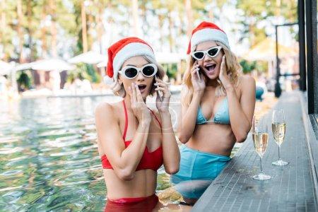 Foto de Dado una sacudida eléctrica las mujeres en trajes de baño y sombreros de santa, hablando de smartphones mientras estaba sentado en la piscina con copas de champagne - Imagen libre de derechos