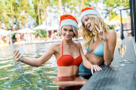 Photo for Beautiful friends in santa hats taking selfie on smartphones while sitting in swimming pool with champagne glasses, girl showing peace symbol - Royalty Free Image