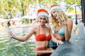 beautiful friends in santa hats taking selfie on smartphones while sitting in swimming pool with champagne glasses, girl showing peace symbol