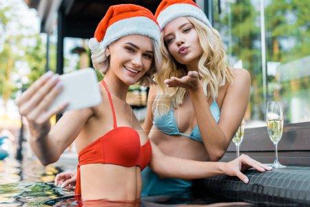 Foto de Amigos felices con sombreros de santa teniendo selfie en teléfonos inteligentes mientras estaba sentado en la piscina con copas de champagne, chica que sopla un beso - Imagen libre de derechos