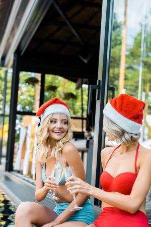 Foto de Hermosas chicas felizes con sombreros de santa que tintinea con copas de champán y sentado junto a piscina - Imagen libre de derechos