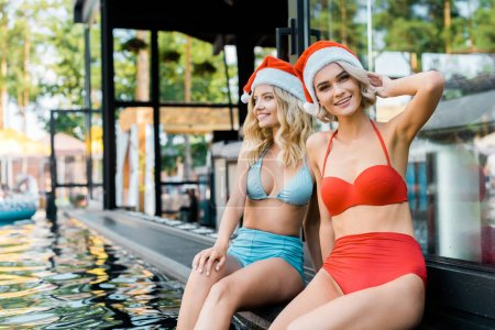 Photo for Beautiful girls in swimsuits and santa hats sitting at poolside - Royalty Free Image