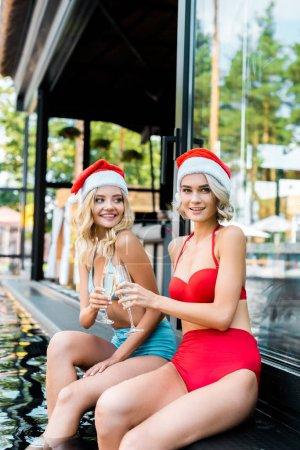Foto de Mujeres hermosas jóvenes en traje de baño y sombreros de santa sosteniendo copas de champagne y sentado junto a piscina - Imagen libre de derechos