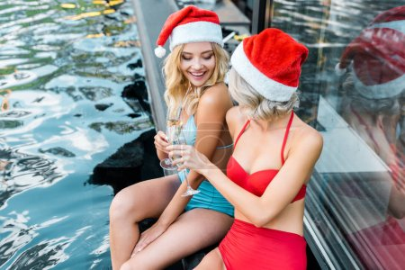 Photo for Cheerful girls in swimsuits and santa hats clinking with champagne glasses and sitting at poolside - Royalty Free Image