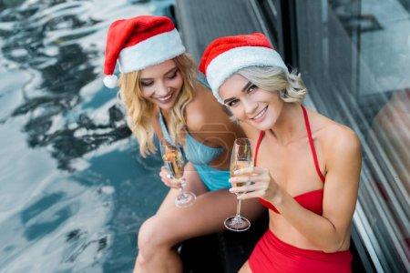 Foto de Chicas felices en trajes de baño y sombreros de santa sosteniendo copas de champagne y sentado junto a piscina - Imagen libre de derechos