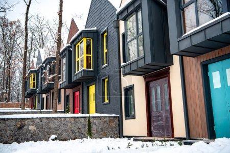 Photo pour Maisons modernes fantaisie avec de la neige sur le sol près des arbres - image libre de droit