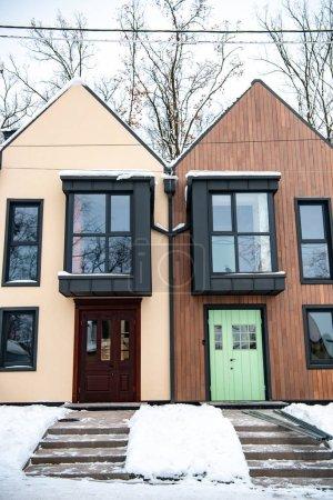 Photo pour Bâtiments modernes élégants avec neige sur les toits près des arbres - image libre de droit