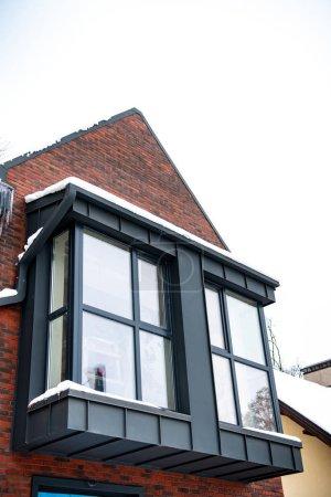 Photo pour Gros plan d'une maison luxueuse avec des fenêtres en hiver - image libre de droit