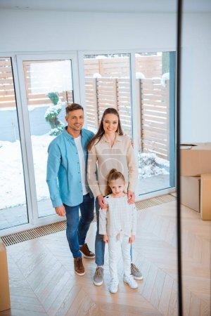 Photo pour Heureux mari et femme debout près de la fille cute dans maison neuve - image libre de droit