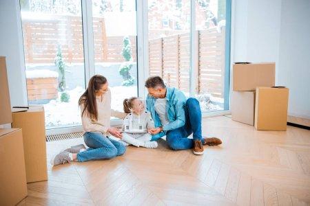 Foto de Padre feliz mirando hija con la casa modelo en las manos cerca de esposa sentado en piso en nueva casa - Imagen libre de derechos