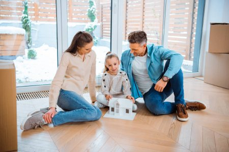 Photo for Happy husband and wife looking at cute daughter with house model in hands while sitting on floor in new home - Royalty Free Image