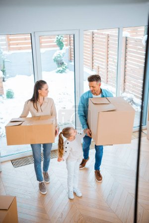 Photo for Cute daughter looking at cheerful mother and father holding boxes in new home - Royalty Free Image