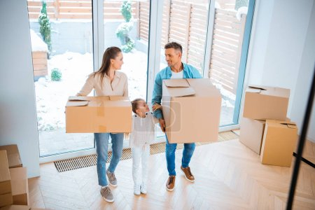 Photo pour Enfant debout entre la mère gaie et le père en se regardant tout en tenant des boîtes dans une nouvelle maison - image libre de droit