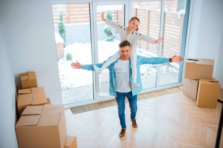 Photo for Cheerful father carrying on neck smiling daughter while walking in new home - Royalty Free Image