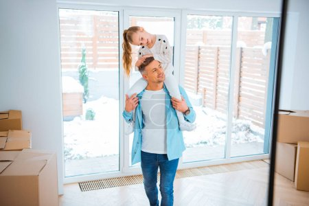 Photo for Handsome father carrying on neck smiling daughter while walking in new home - Royalty Free Image